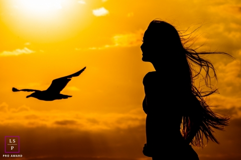 Santa Catarina sunset teen portrait as a silhouette with a seabird in flight during this Brazil session