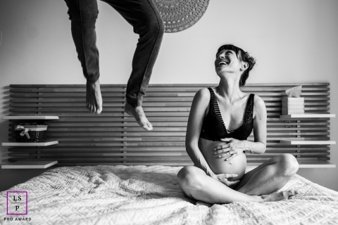 Perpignan lifestyle indoor maternity image session during couple in bedroom, father jumping on bed