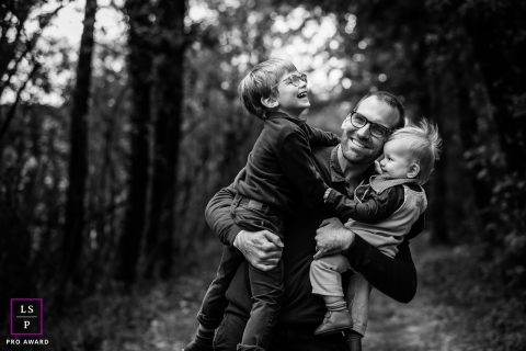 Bourgogne-Franche-Comte dad is strong during a black and white France family photo session in the woods