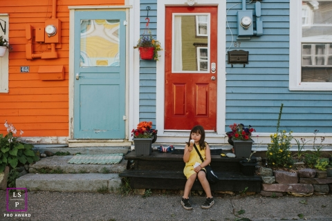 Artistic Toronto Lifestyle Photography showing A little girl in a yellow dress eats an ice cream on the steps of a row house in St. John's, Newfoundland
