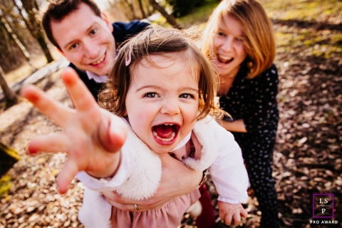 Auvergne-Rhone-Alpes Lifestyle Family Photographer created this artistic portrait of A family having fun while The little girl tries to save herself from her parents