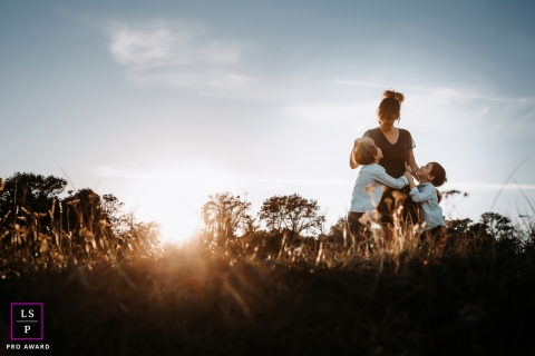 Ain Lifestyle Family Photographer created this artistic portrait of a mom with her children during sunset