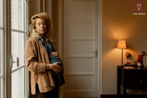 Besancon Maternity Lifestyle Photographer created this artistic portrait of a mum-to-be standing near a window