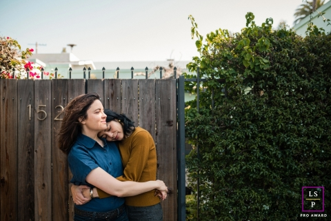 LA couple posing for a creative Lifestyle image hugging one another by wood fence