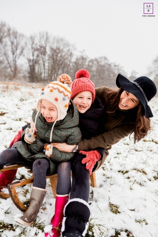 Groningen Family posing for a Lifestyle portrait sitting on a sled in the snow