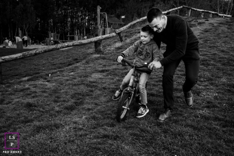 Flanders father and son pose for a Lifestyle portrait as father pushes child on bike