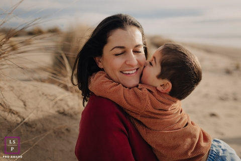Herault family lifestyle portrait of a boy kissing his mom on the cheek on the sands of the beach