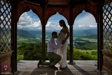 Costa Rica Mother and Father posing for a Lifestyle Maternity Portrait as a silhouette inside a little gazebo with a beautiful landscape behind in Hacienda Sitio de Mata, Turrialba