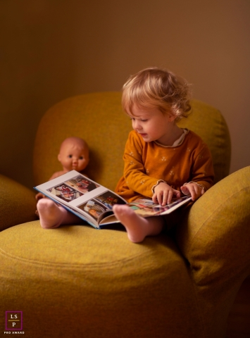Zwolle young child poses for a Lifestyle Portrait Session with a book and dool on a livingroom chair