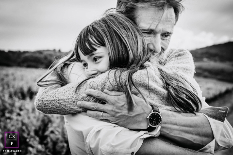 Auvergne-Rhone-Alpes father and daughter pose for a Lifestyle portrait as they embrace in a big hug