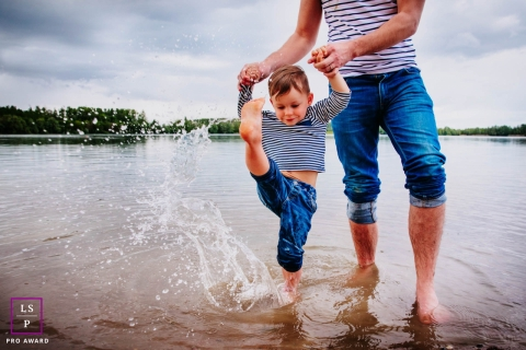 France father and son pose for a Lifestyle Portrait Session as the boy kicks his feet in the water