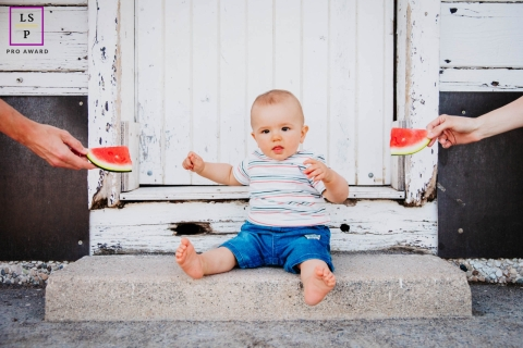 France toddler poses for a Lifestyle Portrait Session as the boy is little boy has a choice for his share of watermelon. Mom and Dad want to know which of the two he will choose