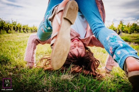 Auvergne-Rhone-Alpes young girl poses for a Lifestyle Portrait Session as she rolls in the grass