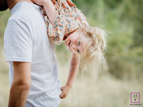Amboise young girl poses for a lifestyle photo as she hangs upside down over the shoulder of her father