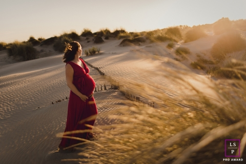 Herault woman poses for a lifestyle maternity photo session during a windy sunset