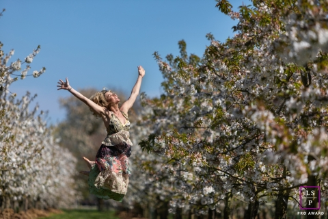 Gelderland woman poses for a Lifestyle Portrait Session jumping up amongst blossoming trees