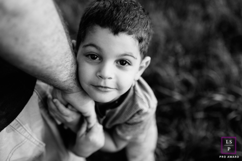 Savoie boy poses for a Lifestyle Portrait Session looking up while holding his father's hand