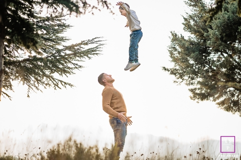 Perpignan Family posing for a Lifestyle portrait as a father throws his son high in the air