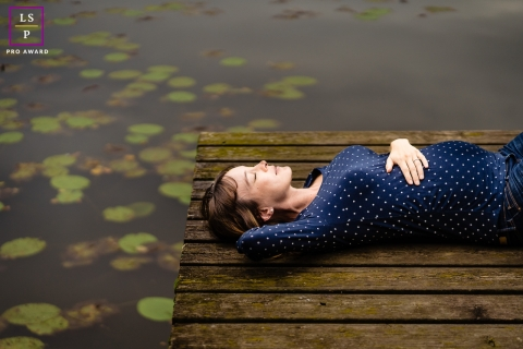 Perpignan woman poses for a Lifestyle Maternity Portrait with some Quiet resting on the wooden dock by the water