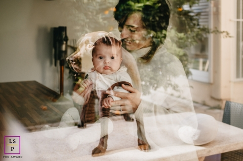 Perpignan Family posing for a Lifestyle portrait session at home with dog reflecting on their window France