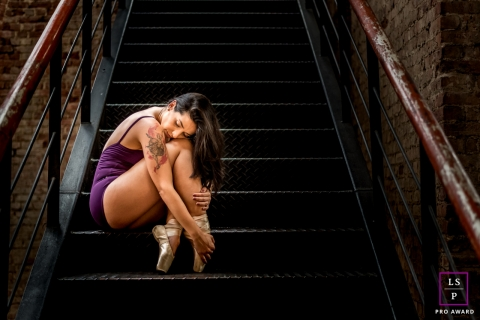 Rio de Janeiro young woman poses for a Lifestyle Ballet photo session illustrating a Dancer staging a sad and lonely moment on the stairs.