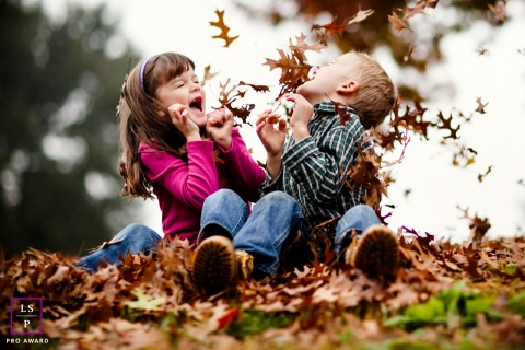 California Kids Lifestyle portrait showing Playing with CA autumn leaves is super FUN