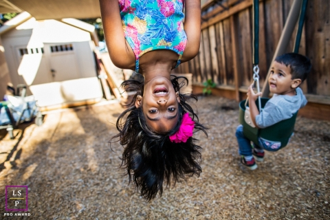 Northern California girl hanging upside-down on a swing for a Lifestyle portrait