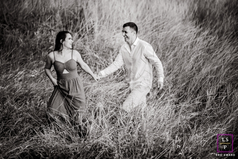 Lifestyle portrait in black and white of the Minas Gerais couple walking through the tall grass