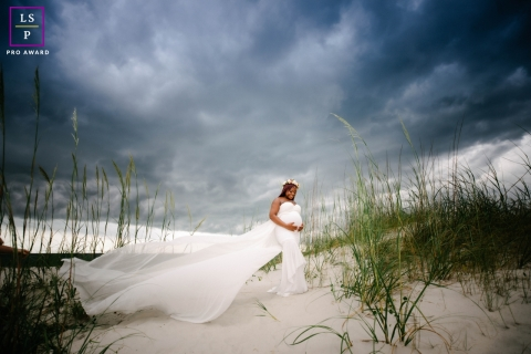 This is a lifestyle photo from Miami of the mom during Maternity shot on the sand in the storm