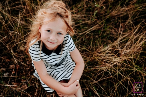 This is a lifestyle picture from France from a Little girl portrait session on the grass