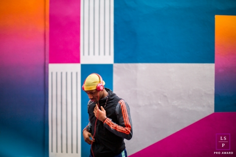 This is a lifestyle image from Biarritz of a man against a colorful painted wall wearing a beanie and headphones and giving off a basketball feeling