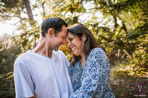 This is a lifestyle image from San Francisco of the married couple in sunlight under trees and head to head