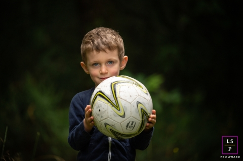 This is a lifestyle photo from Limoges, France of a boy holding a soccer football