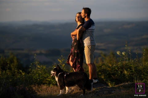 This is a lifestyle picture from Haute-Vienne, France of a couple embracing with their dog on the mountain