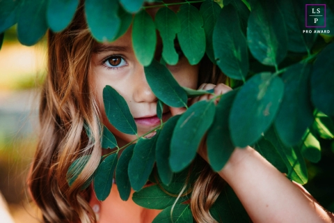 This is a lifestyle Portrait of a shy little girl in France hiding behind tree leaves and only showing one eye