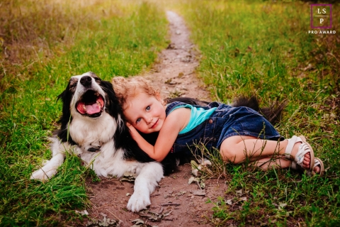 This is a lifestyle photo of A little girl who found the best of pillows in her dog in Auvergne-Rhone-Alpes, France