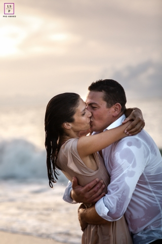 This is a lifestyle image of a couple kissing After the rain in Guadeloupe at the beach