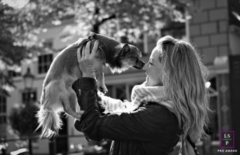 This is a lifestyle image from Utrecht, Netherlands of a woman picking up her dog, her best friend