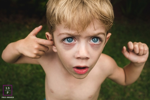This is a lifestyle picture of a boy with his finger in his ear in Mato Grosso do Sul, Brazil