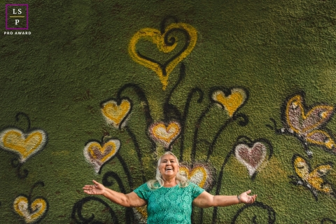 This is a lifestyle image from Campo Grande of a woman standing before a heart and butterfly flower mural and emanates love