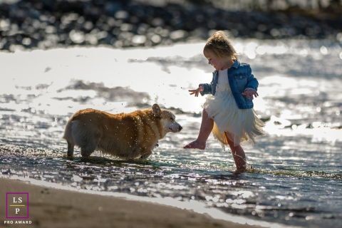 This is a lifestyle photo from California showing a girl and her dog play in the surf