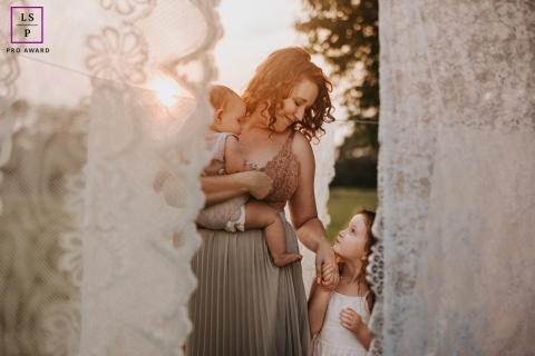 This is a lifestyle image of motherhood in lace curtains outdoors with sunshine in Portland, Oregon