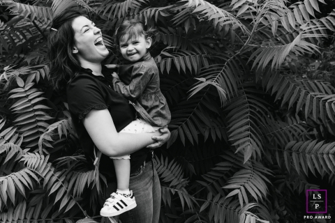 This is a lifestyle photo from Doubs of a young child in the ferns with mom in BW