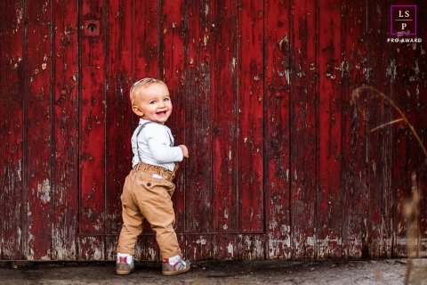 This is a lifestyle image of a small boy against a red painted barn wall in Perpignan