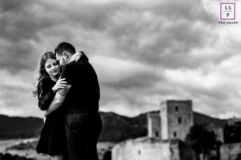 This is a lifestyle photo from Collioure, France of a couple embracing under the clouds by a castle