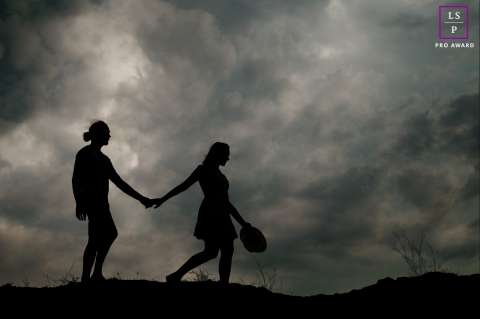 This is a lifestyle image from Perpignan of a Couple at sunset walking hand in hand against clouds