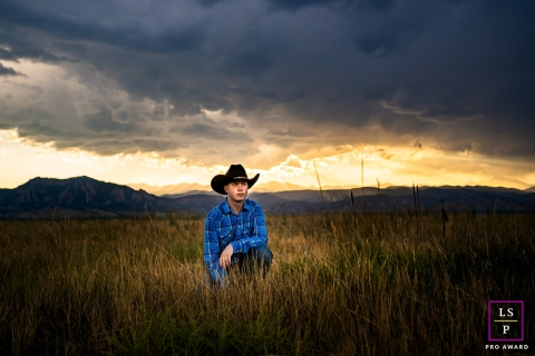 This is a lifestyle picture of a young cowboy in his hat in a grass field in Boulder, Colorado
