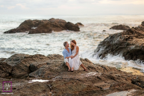 This is a lifestyle image on a beach in Costa Rica with the couple sitting on the rocks with the crashing waves behind