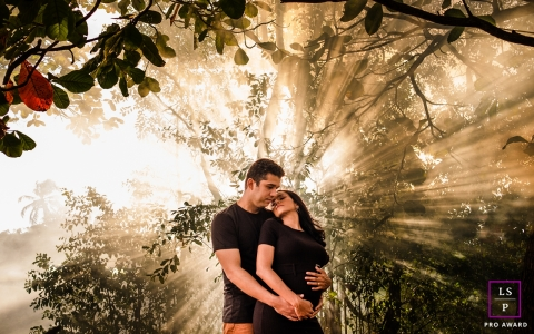 This is a lifestyle picture of man embracing his pregnant woman and in the background a strong light embraces them in Maceio, Alagoas