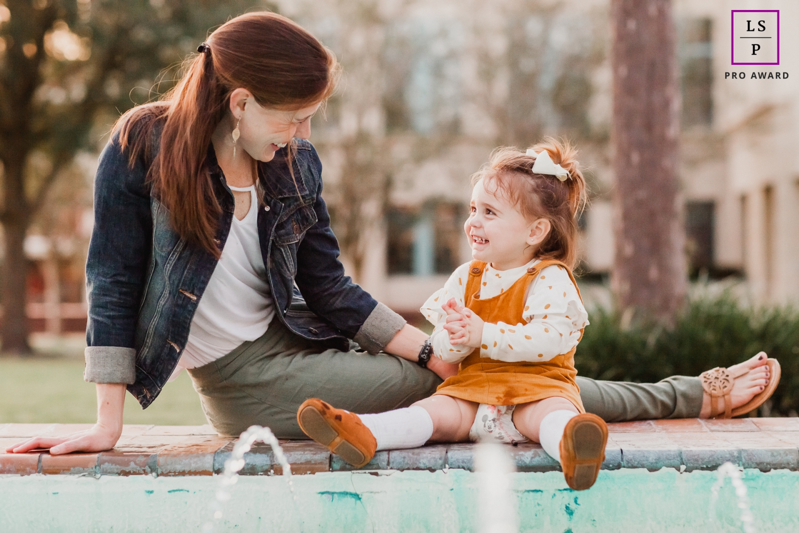 Orlando Mom & daughter sitting on fountain sharing a precious moment during this Florida Lifestyle photo session